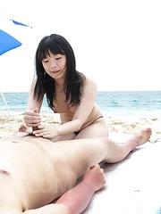 Hina Maeda Asian licks balls and rubs tool with feet on beach